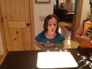 Thea blowing out candles